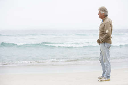 Senior Man On Holiday Standing On Winter Beach Stock Photo - 8482878