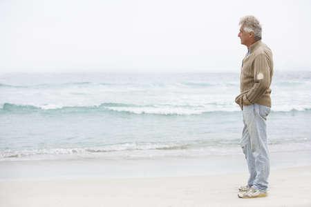 Senior Man On Holiday Standing On Winter Beach Stock Photo - 8482878