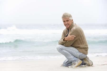 Senior Man On Holiday Kneeling On Winter Beach Stock Photo - 8483004