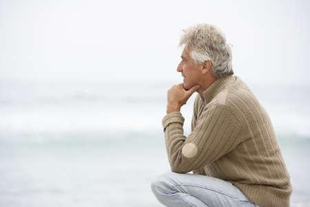 Senior Man On Holiday Kneeling On Winter Beach Stock Photo - 8483127