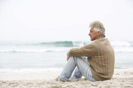 Senior Man On Holiday Sitting On Winter Beach Stock Photo - 8482975
