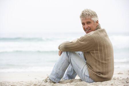 Senior Man On Holiday Sitting On Winter Beach Stock Photo - 8483206