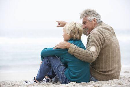 Grandfather And Son Sitting On Winter Beach Together photo