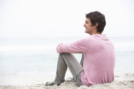 Young Man On Holiday Sitting On Winter Beach Stock Photo - 8483042