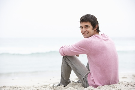 Young Man On Holiday Sitting On Winter Beach photo