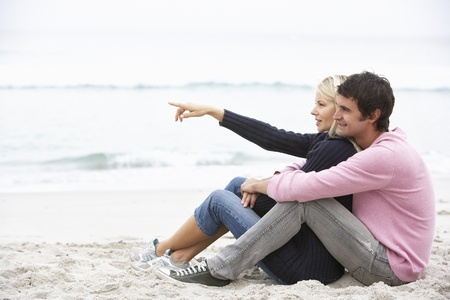 loving couples: Young Couple On Holiday Sitting On Winter Beach