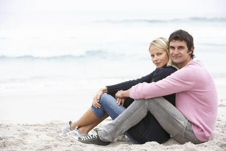 Young Couple On Holiday Sitting On Winter Beach Stock Photo - 8483152