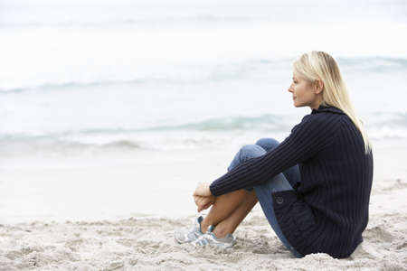 Young Woman On Holiday Sitting On Winter Beach Stock Photo - 8482954
