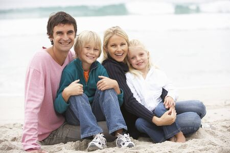 5 10 year old girl: Young Family Sitting On Winter Beach Stock Photo