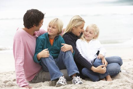 causal clothing: Young Family Sitting On Winter Beach Stock Photo