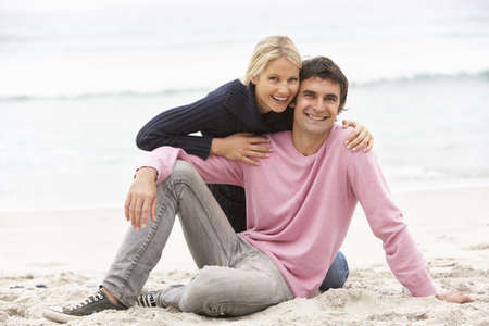 Young Couple On Holiday Sitting On Winter Beach photo