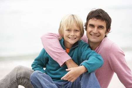 Father And Son Sitting On Winter Beach Together photo