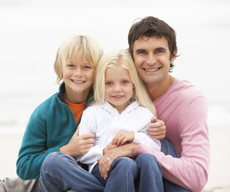 causal clothing: Father And Children Sitting On Winter Beach Together