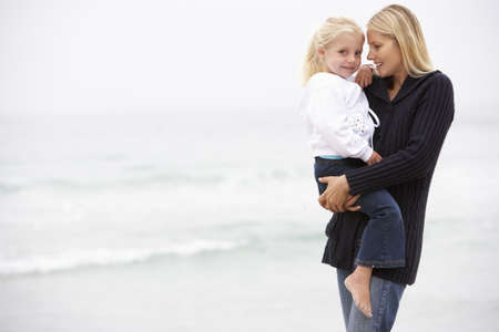 Mother And Daughter On Holiday Standing On Winter Beach photo