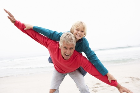 piggyback ride: Grandfather Giving Grandson Piggy Back On Winter Beach