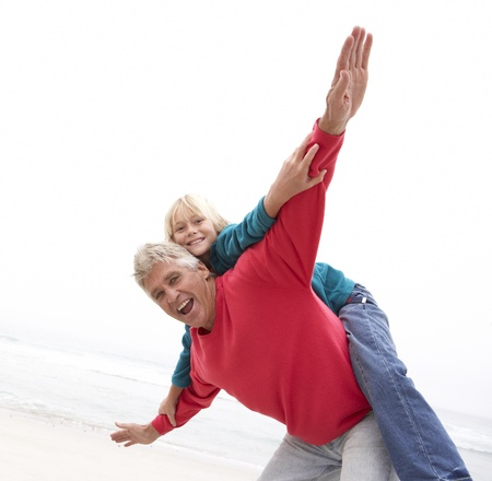 causal: Grandfather Giving Grandson Piggy Back On Winter Beach