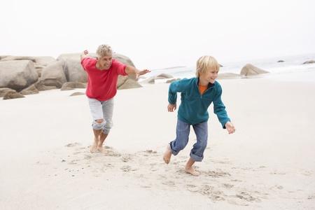 Grandfather Chasing Grandson Along Winter Beach photo
