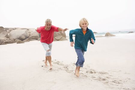 ten year old: Grandfather Chasing Grandson Along Winter Beach