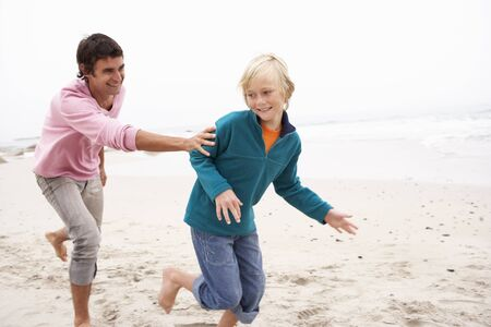 causal clothing: Father Chasing Son Along Winter Beach