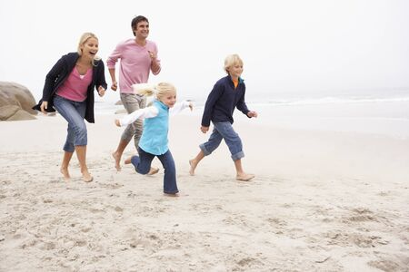 5 10 year old girl: Young Family Running Along Winter Beach