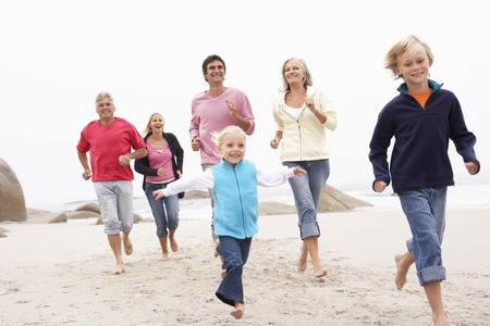 a generation: Three Generation Family Running Along Winter Beach Together