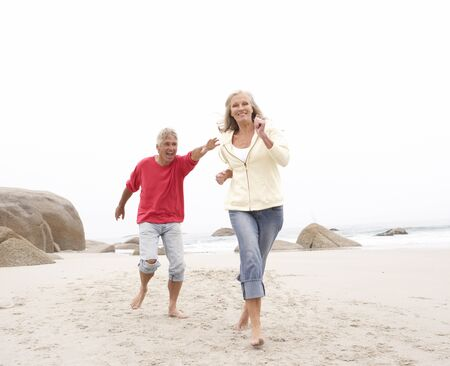 Senior Couple On Holiday Running Along Winter Beach Stock Photo - 8482835