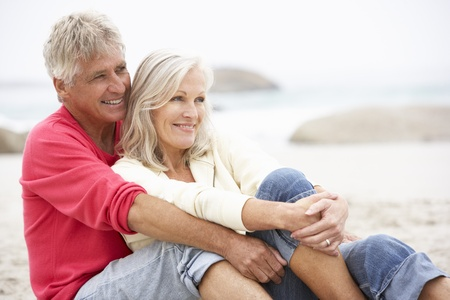 elderly couples: Senior Couple On Holiday Sitting On Winter Beach