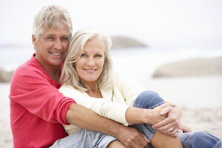 Senior Couple On Holiday Sitting On Winter Beach photo