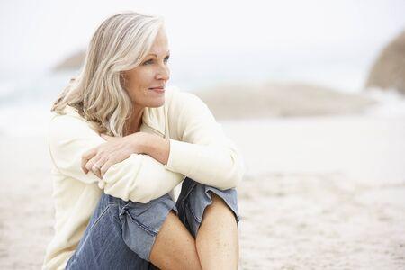 Senior Woman On Holiday Sitting On Winter Beach Stock Photo - 8482942