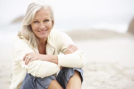 mujeres sentadas: Mujer Senior de vacaciones sentado en la playa de invierno