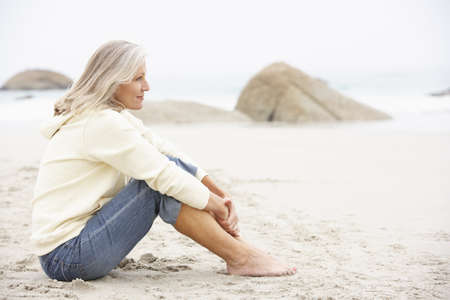 Senior Woman On Holiday Sitting On Winter Beach photo