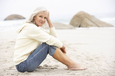 Senior Woman On Holiday Sitting On Winter Beach Stock Photo - 8483064