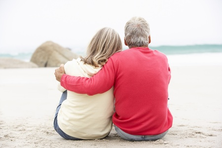 shoreline: Senior Couple On Holiday Sitting On Winter Beach