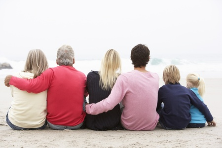 Vue arrière de la famille de trois générations assis sur la plage d'hiver ensemble