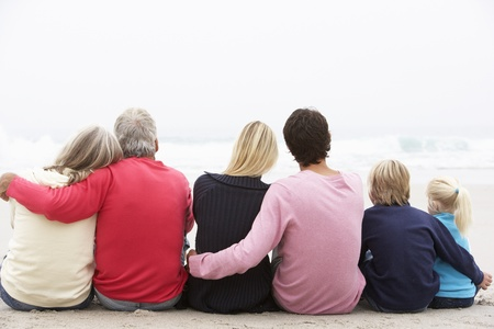Back View Of Three Generation Family Sitting On Winter Beach Together photo