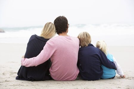 causal: Back View Of Young Family Sitting On Winter Beach