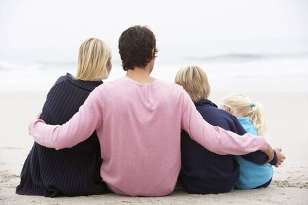 familia de cinco: Vista de familia joven sentado en la playa de invierno posterior Foto de archivo