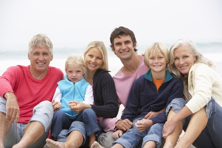 causal: Three Generation Family Sitting On Winter Beach Together Stock Photo