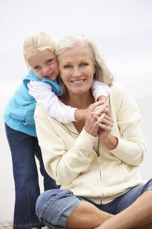 grandmother children: Abuela y nieta de vacaciones sentado en la playa de invierno