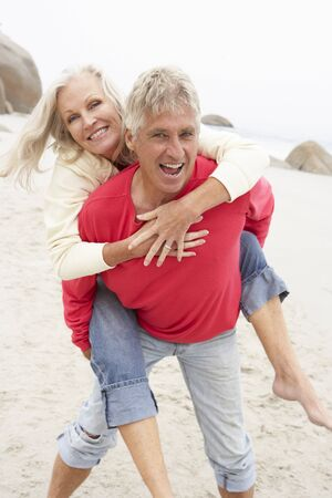 Senior Man Giving Woman Piggyback On Winter Beach Stock Photo - 8482971