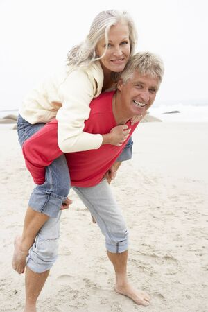 active holiday: Senior Man Giving Woman Piggyback On Winter Beach