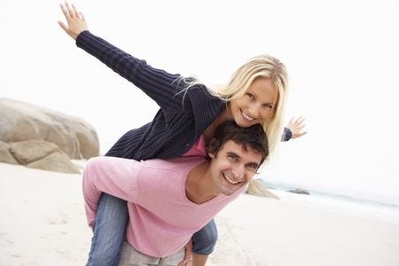 Man Giving Woman Piggyback On Winter Beach Stock Photo - 8476470