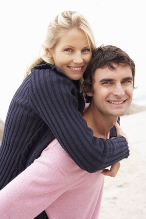 Man Giving Woman Piggyback On Winter Beach Stock Photo - 8483303