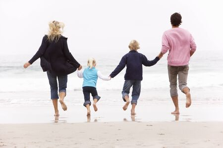 Back View Of Young Family Running Along Winter Beach Stock Photo - 8482833