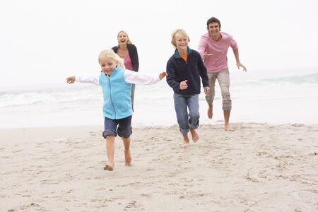 Young Family Running Along Winter Beach Stock Photo - 8483154