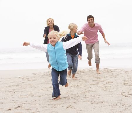 Young Family Running Along Winter Beach photo
