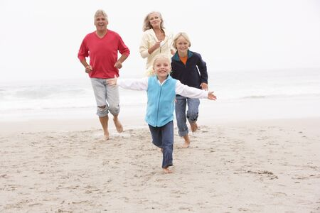 grandparent: Grandparents And Grandchildren Running On Winter Beach Together