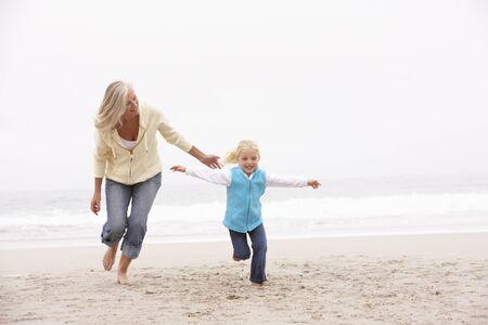grandmother children: Abuela y nieta a lo largo de la playa de invierno