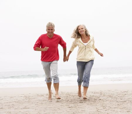 active holiday: Senior Couple On Holiday Running Along Winter Beach