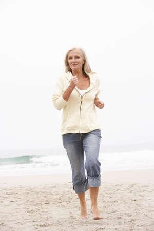 Senior Woman On Holiday Running Along Winter Beach Stock Photo - 8482891